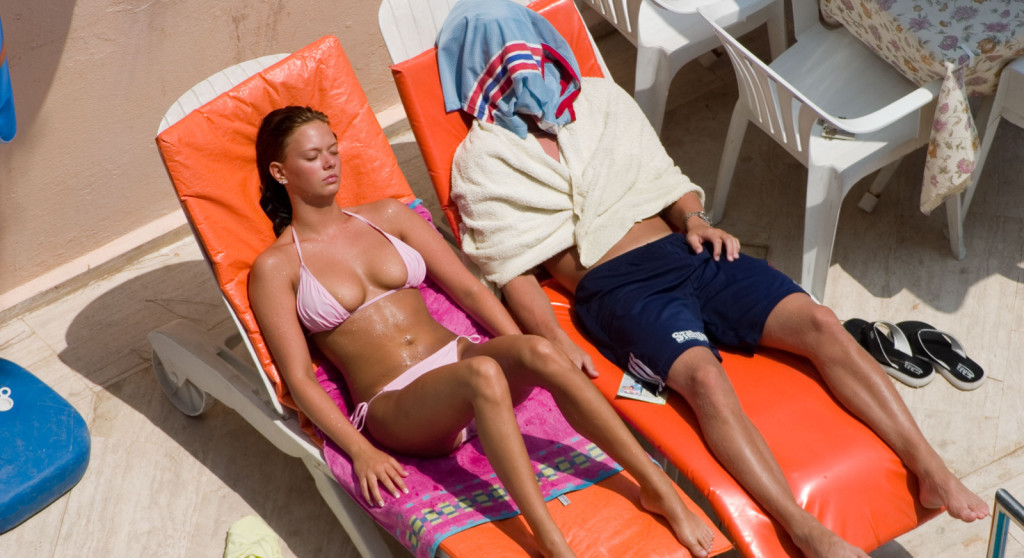 couple sunbathing - one covered one uncovered